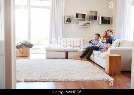 Famiglia seduti sul divano a casa a guardare la TV insieme Foto Stock