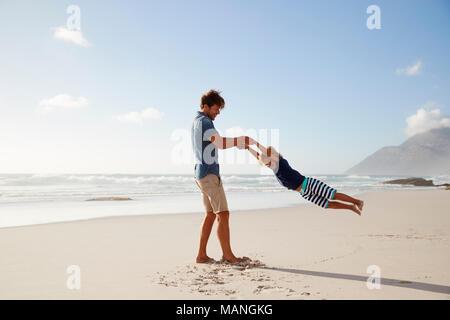 Padre divertendosi con figlio d'estate vacanza in spiaggia Foto Stock