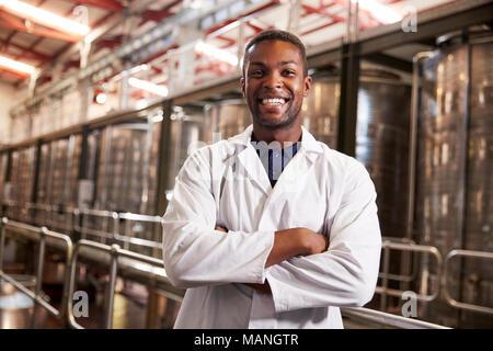 Giovane maschio nero fabbrica del vino tecnico sorridente alla fotocamera Foto Stock