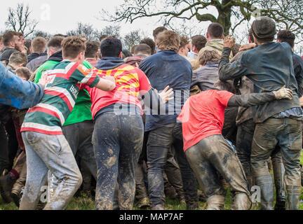 Gli abitanti di un villaggio da Hallaton bagarre con il rivale gli abitanti di un villaggio dal vicino villaggio di Medbourne in una ruvida incontro sul bagnato e fangoso la campagna in hea Foto Stock