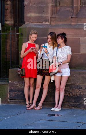 Due giovani ragazze e donna di mezza età guardando i loro telefoni cellulari, Strasburgo, Alsazia, Francia, Europa Foto Stock