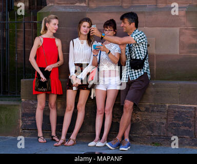 Due giovani ragazze, di mezza età della donna e uomo che guarda i loro telefoni cellulari, Strasburgo, Alsazia, Francia, Europa Foto Stock