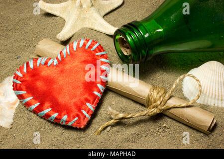 Il messaggio e il cuore rosso amore . Un rotolo di carta in una bottiglia sulla sabbia. Conchiglie di mare. Foto Stock