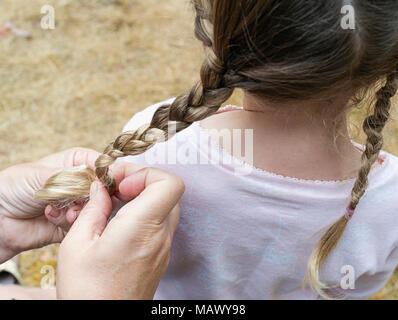 Una donna trecciatura in giovani ragazze capelli. Foto Stock