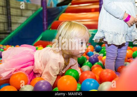 Bambina giocando in una piscina di palline Foto Stock