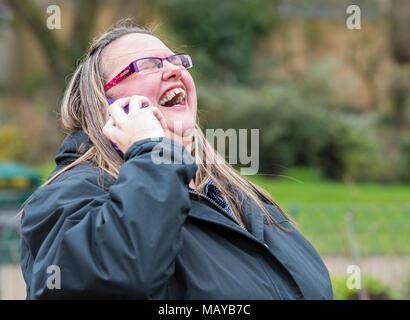 Giovane donna ridendo e guardando felice mentre godendo di una conversazione telefonica con un amico. Concetto di felicità. Avendo una risata. A ridere con gli amici. Foto Stock
