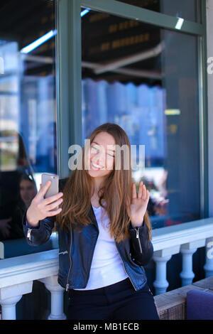 Bella donna fare chiamata video tramite smartphone al cafe.