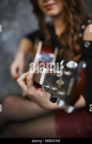 Giovane ragazza in un rosso minigonna in pelle e collant nero a suonare la chitarra, close-up, la profondità di campo. Foto Stock