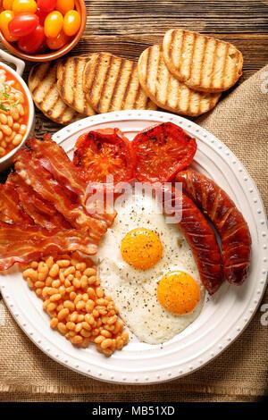 Prima colazione inglese con salsicce, pomodori grigliati, uova, pancetta, fagioli e pane sulla piastra bianca Foto Stock