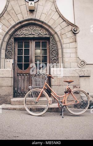 Pink bike parcheggiata di fronte le porte di una casa stile liberty con una decorazione a rilievo. Helsinki - Finlandia Foto Stock