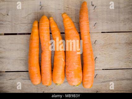 Materie le carote fresche su uno sfondo di legno. Foto Stock