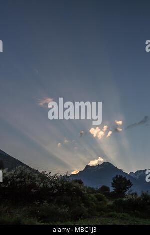 Le alte montagne che circondano Jispa significa che la luce del sole è visto come fasci luminosi la rottura oltre le creste inferiori quando si sale al mattino Foto Stock