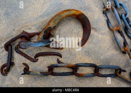 Rusty corrosi e anello di ormeggio, la catena e il grillo giacente nella sabbia sulla spiaggia di Porto th gat st Ives sul litorale della Cornovaglia. Foto Stock