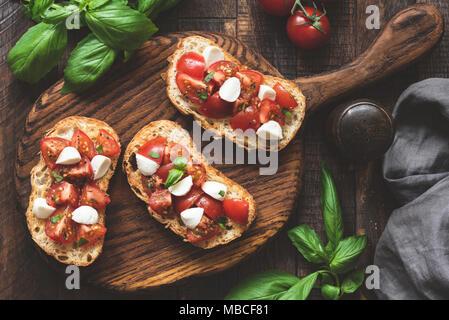 Italiano antipasti bruschetta con pomodoro, mozzarella e basilico sul pannello di legno. Vista superiore, tonica immagine Foto Stock