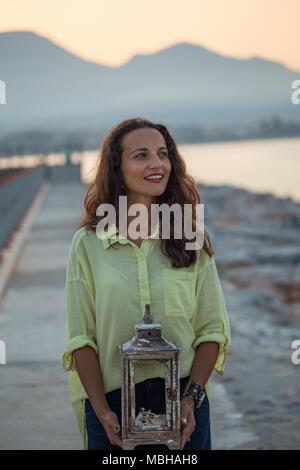 Donna sorridente con scuri capelli ondulati indossando giallo maglietta di cotone azienda rustico in legno lanterna nelle sue braccia e sorridente. Foto Stock