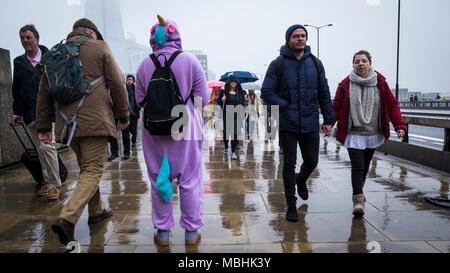 Londra, Regno Unito. 11 aprile 2018. Regno Unito Meteo: una raccolta di fondi per la Meningite Research Foundation si erge su London Bridge come passare i pendolari fanno il loro modo di lavorare su un drizzly giornata nella capitale (c) Paolo Swinney/Alamy Live News Foto Stock