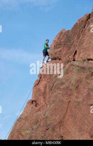 Scalatore di arrampicata uomo scogliere di arenaria nel Giardino degli dèi Aprile 4, 2016
