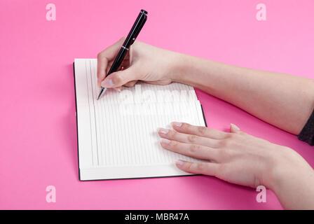 La donna la scrittura a mano utilizzando una penna in notebook isolato su sfondo rosa Foto Stock