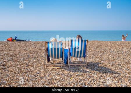 BRIGHTON, Regno Unito - 8 Aprile 2017: giovane seduto in sedie a sdraio su un soleggiato aprile giornata sulla spiaggia di Brighton in aprile 2017. Foto Stock