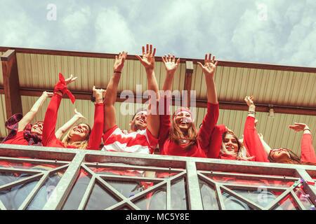 ... Gruppo di fan vestiti di colore rosso a guardare un evento sportivo in  una gradinata di a1799d8aede