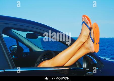 Primo piano di un giovane uomo caucasico, indossando un paio di orange flip-flop, rilassante in un auto accanto agli oceani Foto Stock