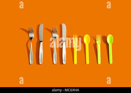 Quattro set di posate su sfondo arancione che rappresenta il concetto di famiglia
