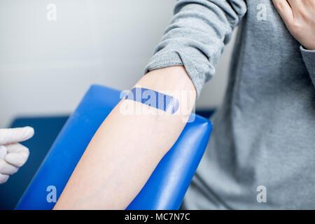 Incollaggio di cerotto adesivo dopo la procedura di assunzione di sangue per il test in laboratorio Foto Stock