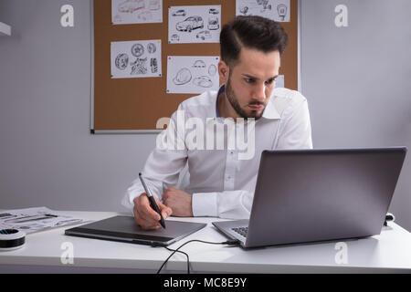 Designer maschio con tavoletta grafica lavorando sul computer portatile Foto Stock
