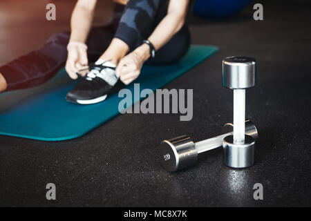 Giovane attraente ragazza bruna enlacing il suo sport calzature dopo la pratica di allenamento e formazione crossfit su blu materassino yoga. Donna sfocata è su backgroun Foto Stock
