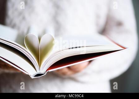 Prenota con pagine aperte e la forma del cuore in girl mani. Copia dello spazio. Il concetto di amore Foto Stock