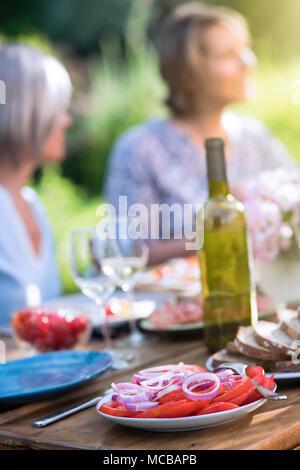 Close-up su una piastra con pomodoro e fette di cipolla in una tabella in un giardino dove gli amici si riuniscono per condividere un pasto. Foto Stock