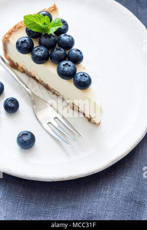Pezzo di cheesecake con mirtilli freschi sulla piastra bianca. Messa a fuoco selettiva Foto Stock