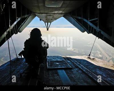 Sgt. Adam Collins, un CH-53E capo equipaggio con Marine elicottero pesante Squadron (HMH) 465, esegue la scansione della zona sotto tra salta durante il volo e le operazioni con il paracadute con la prima ricognizione marina battaglione al Marine Corps base Camp Pendleton, California, 6 feb. Durante il paracadute e operazioni di volo, il combattimento a terra e l'elemento aria elemento di combattimento lavorano insieme per garantire la sicurezza e la missione la realizzazione durante il corso di formazione. (U.S. Marine Corps foto di Sgt. David Bickel/rilasciato)