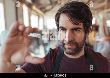 Esperti artigiani giovani con la barba tenendo premuto fino ed esaminando un pezzo di vetro mentre in piedi nella sua officina Foto Stock