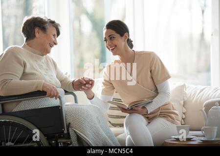 Senior in una sedia a rotelle e belle infermiere sorridente e tenendo le mani durante la lettura di un libro Foto Stock