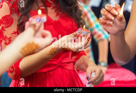 Le mani e le dita sono disegnati per henna . Femmina con mano henna tattoo . . Essa detiene la candela in mano Henna party Foto Stock