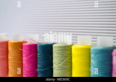 Vari fili colorati con vestiti pulsanti sul cartoncino bianco dello sfondo.
