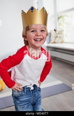 Ritratto di giovane ragazzo, indossa una corona di cartone, sorridente Foto Stock