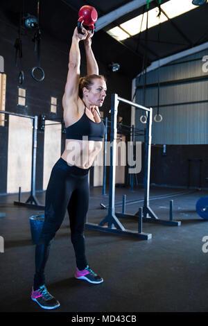 Donna esercizio in palestra, utilizzando kettlebell Foto Stock