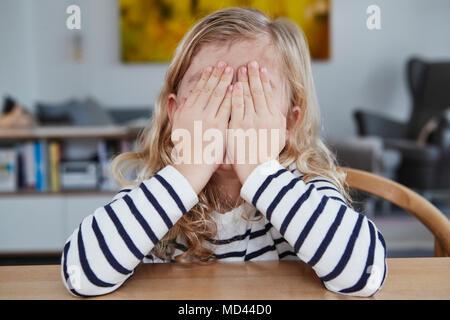 Ritratto di giovane ragazza seduta a tavola, che ricopre la faccia con le mani Foto Stock