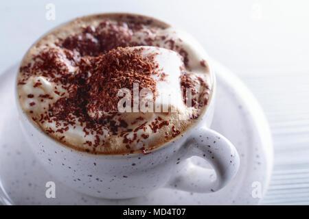 Cioccolata calda e marshmallow cosparso con scaglie di cioccolato bianco su un tavolo di legno. Foto Stock