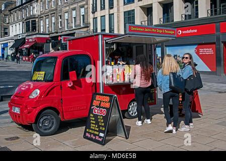 I clienti ad un hotdog stallo in Princes Street, Edimburgo, Scozia, Regno Unito. Foto Stock