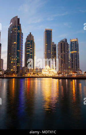 La moschea di illuminati sotto architettura moderna e torri riflessa in acqua a Dubai Marina, Dubai, Emirati Arabi Uniti, Medio Oriente Foto Stock