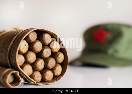 ... Alcuni sigari cubani laminato in foglia di banano e cappello militare  sullo sfondo Foto Stock 951ed73be760