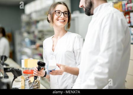 I farmacisti che lavorano in farmacia store Foto Stock