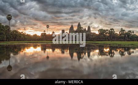 Cambogia antico tempio complesso Angkor Wat a sunrise con drammatica nuvole sopra le torri e la riflessione in Stagno. Famosa destinazione di viaggio. Foto Stock