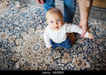 Padre con una bambina a casa. Primi passi. Foto Stock