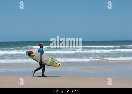 Surfista maschio che trasportano le tavole da surf, indossando il corpo pieno muta passeggiate sulla spiaggia di Praia do Rosa, Brasile. Foto Stock