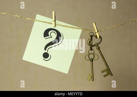 Chiave Vintage appeso a una fune sul fondo oro, adesivo successivo con punto interrogativo Foto Stock