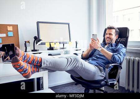 Rilassata uomo seduto alla scrivania in ufficio tramite telefono cellulare Foto Stock